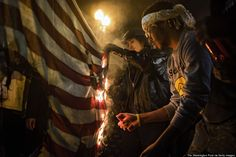 The 52 Best Photographs From Around The World In 2014 WASHINGTON, DC - NOVEMBER 25: Protesters burn a US flag as they march through downtown Washington, DC following a Missouri grand jury's decision not to indict Officer Darren Wilson in Washington November 25, 2014.