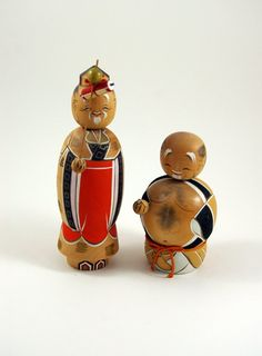"""This particular style of kokeshi is called """"shingata,"""" which is also known as """"creative"""" kokeshi. In this style, artists have freedom to experiment with different shapes and styles. This pair is particularly noteworthy for the detailed painting on each figure"""