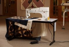 George is a stationary, sit-down longarm quilting machine with a generous throat space and a large, flat work-space to easily maneuver your quilt.