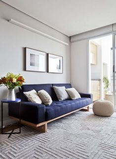 Sala com elementos neutros e sofá azul marinho.