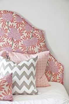 Upholstered headboard (love the shape!) and lots of pillows layered on for color and texture. {design by Caitlin Wilson}