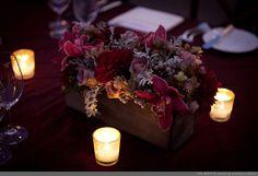Burgundy and grey flower arrangement in old box