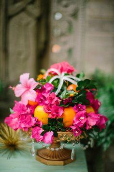 Colourful bougainvillea, hibiscus and orange centerpiece. Ruffled – photo by http://bestphotographyfl.com – http://ruffledblog.com/florida-spring-wedding-ideas/