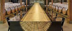 O projeto é do designer John Houshmand e chama a atenção especialmente por usar um imenso tronco de árvore aberto ao meio, revelando o seu interior, e também pelo contraste da madeira ao natural com o vidro.  Na base, painéis de aço suportam o tronco inteiro e no topo, o tampo de vidro nas laterais completa a mesa de 30 lugares. A mesa foi feita para a vinícola Hall Winery, em Napa Valley, na Califórnia, uma região de amplo cultivo de vinho, e instalada em meio aos barris, também de madeira.