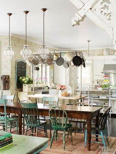 """Few things emanate """"country cottage"""" more clearly than mismatched chairs pulled up to a long, wooden farm table. The busy floral wallpaper and bustling pot rack in this lively kitchen make it the perfect space to play host to all manner of friends and family./"""