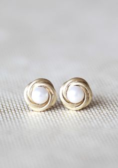 """Venetian Pearl Earrings 12.99 at shopruche.com. Coiled golden hued swirls hold luminescent faux pearls on these understated studs.0.5"""" diameter"""