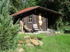 Das Saunahäuschen im Garten mit Carving, Designerstühlen und Außendusche