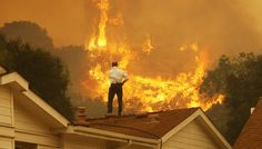 A man on a rooftop looks at approaching flames as the Springs Fire continues to grow on May 3 near Camarillo, Calif. The wildfire has spread to more than 18,000 acres on day two and is 20 percent contained.