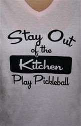 Take advice from the shirt: Stay out of the kitchen - play pickleball! This fun shirt will be sure to make you stand out in the crowd. The V-neck shirt is light pink with cursive black lettering. It is made of Hanes 100% preshrunk breathable cotton for casual or athletic wear. Available in PINK only, sizes are Ladies' Small, Medium, L, and XL  $19.99