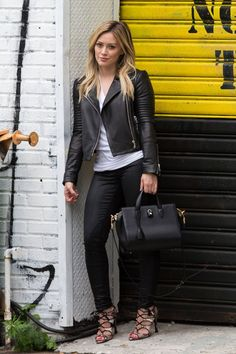 Shop this look on Lookastic: https://lookastic.com/women/looks/biker-jacket-crew-neck-t-shirt-skinny-jeans-heeled-sandals-tote-bag/8475 — White Crew-neck T-shirt — Black Leather Biker Jacket — Black Skinny Jeans — Black Leather Tote Bag — Beige Snake Leather Heeled Sandals