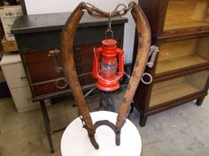 Small horse hames and a horse shoe repurposed into a lantern holder.