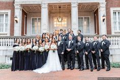 Bridal party photography in front of brick mansion, navy velvet bridesmaid dresses