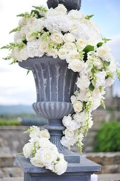Wedding Flower Arrangements A large gray urn is filled with a cascade of white roses, hydrangeas and freesia. Floral Centerpieces, Wedding Centerpieces, Floral Arrangements, Wedding Bouquets, White Roses, White Flowers, Beautiful Flowers, Cascading Flowers, Alter Flowers