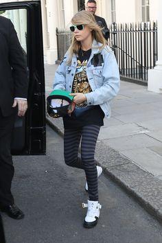 Cara Delevingne threw a Levi's denim jacket over her printed tee, striped leggings, Nike Air Jordan sneakers, and green sunglasses in London.