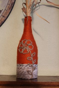 This re-purposed wine bottle is wrapped with various colored yarns and twine. Each bottle has a detailed sailboat made from twine. They make great