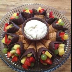 Looks yummy!! Ice cream cones dipped in chocolate & filled with fruit. Serve with fruit dip in the middle.