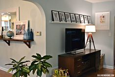 House Tour: Living Room - I like the shlef with all same size frames in a row!