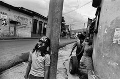 """by Larry Towell. """"This shot was taken in El Salvador. Child with star mask during """"Day Of The Dead"""". Other child in background rolls tire for repair in garage where he works at an adult's job."""""""