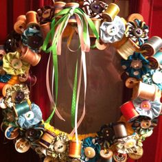 Wreath decorated with spools of thread, fabric layers, and buttons - SO CUTE!
