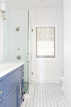 White and blue bathroom features a blue washstand adorned with long polished nickel pulls topped with white quartz.
