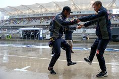 Daniel Ricciardo of Australia and Infiniti Red Bull Racing and Daniil Kvyat of Russia and Infiniti Red Bull Racing dance in the pit lane to entertain...