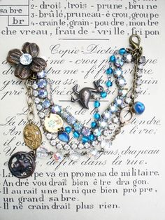It's Complicated 4 Strands Bracelet in Blues with Duck  I think these bracelets are my favorite type to make. They represent what repurposing really means. I'm taking bits and pieces, leftover links, etc. and combining them all into a new cool design!   Strand number 1 and 2 are single strand rhinestone bracelets. One is all clear prong-set stones and the other has larger clear prong-set stones with an aurora borealis coating...