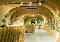 The Martian Embassy in Sydney Australia by LAVA 'Using a fluid geometry merging the 3 program components [embassy, school & shop], a computer model was sliced & 'nested' into buildable components. 1068 pieces of CNC-cut plywood were used. The timber ribs create shelves, seats, benches, storage, counters and displays & continue as strips on the floor. Edged with green, the curvy plywood flows seamlessly so that walls, ceiling & floor, space, structure & ornament, become 1 element.'