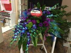 Dendrobium orchids & carnations of dark purples & blues with aspidistra leaves & other greenery casketspray for a volleyball player by Donna Jeffries & Cyndy Smith