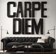 "seize the day... oversized letters spelling ""carpe diem"" in place of artwork above large vintage leather chesterfield sofa"