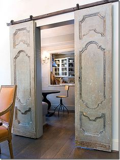 image Antique doors from dining room into kitchen.  The apricot of chairs looks nice in in front of the weathered doors.  Dark wood floors.