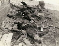 """These dead German Waffen-SS troops were a three-man bazooka team that tried to slow up the advance of an American armored column and were killed by a direct hit"""