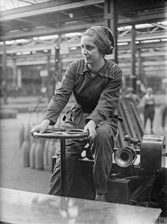 A portrait of a woman war worker as she drives her trolley around the factory floor at the National Shell Filling Factory, in Chilwell, Nottinghamshire. She is wearing overalls and a cap. 1914-1918