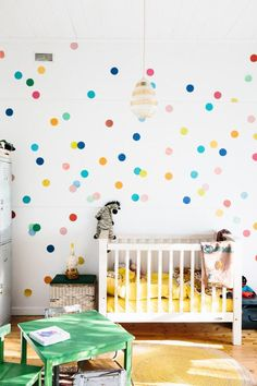 """""""We wanted Syd's room to feel really happy and bright. The colored spots are an afternoon project he helped with. The little beehive lamp is a lucky garage sale score and that is Michael's old scouts' blanket hanging over the cot."""""""