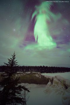 Through a window in the clouds aurora Borealis (the Northern Lights) appear in a spooky form over winter landscape of northern Canada. Yuichi Takasaka, Blue-moon.ca