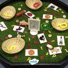 Practise phonics with this tuff tray exploration area. Ask children to sort the objects by their initial sounds for a fun and interactive language activity. Create a Twinkl account and download our sound cards and letters to create your own activity area. #phonics #sounds #letters #words #tufftray #language #primary #school #education #resources #printablesforkids #indoorplay #learning #twinkl #twinklresources