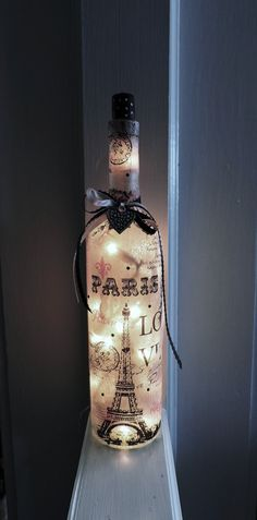 Pink Paris Wine Bottle Lamp/Nite Light 750 ml Bottle  This is a re-purposed liquor bottle thats been transformed into a pretty, pink Paris Lamp. Patterned tissue paper is decoupaged around the entire bottle and includes pink & black ribbon and a metal heart charm attached to the ribbon. The top of the bottle has a re-purposed wine cork that has been painted black with little white polka dots.  There is a small hole drilled into the back of the bottle near the bottom. A string of electric…