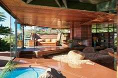 In the living room of Jeremy Scott's circa 1947 John Lautner–designed home in L.A., the architect included a lot of built-in furniture; this furniture, along with the swimming pool, dominates the space, and all the designer had to do was add some lamb-covered bean bags.
