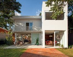 Nos fundos, os arquitetos Tito e Chantal Ficarelli construíram um volume extra. No térreo, fica a sala de jantar aberta para o jardim, assim...