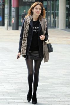 Alexa Chung winter street style: black tee, black peacoat, fur vest, leather skirt, black tights and boots