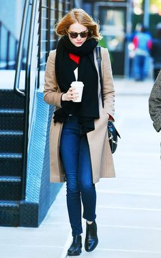 Emma Stone wears a colorblock sweater, camel coat, scarf, skinny jeans, and ankle boots