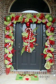 A Whole Bunch Of Christmas Porch DecoratingIdeas - Christmas Decorating - holiday, front door decor, christmas front doors, christma decor, candy canes, garland, porch, deco mesh, christmas door