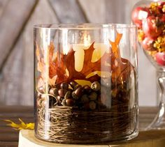 Glass container with candle, leaves, acorns and twigs. Fall Decor