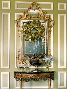 A shimmery gingko-leaf wreath and rococo mirror hang above an early 19th-century console table, where a large antique silver urn chills wine.