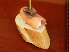 Basque Tapa of Smoked Salmon wrapped around Cream Cheese and garnished with Anchovy