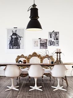 Marie Olsson Nylander dining room, black pendant, wood table, white Saarinen chairs, gold ornate mirror, contemporary black white photography
