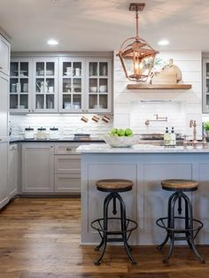 The kitchen's color palette of white, gray and black is nicely offset by copper fixtures including twin sconces, faucets and drawer hardware.