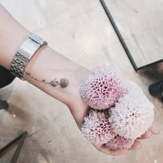 Small flower tattoo on the left wrist. Tattoo artist: Doy