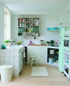 Rustikt køkkenKøkkenmodulerne er dækket af kvadratiske fliser, der sender tankerne tilbage til et gammelt køkken fra 1930-erne. På arbejdsbordet er der lagt en rustik træbordplade, og det lyse rum piftes op med blødt formede hvidevarer samt forskellige detaljer i den grønne og blå farveskala. I køkkenmodulerne er åbne hylder kombineret med rummelige skuffer, og i i stedet for overskabe opbevares stel og dekorative dåser i en væghængt metalreol. Køkkenet er designet og bygget af Det Mondæne…