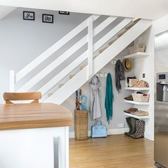 Compact understairs hallway storage with floating shelves and wooden floor