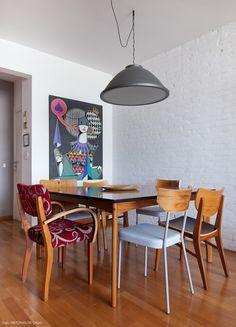 Sala de jantar com mesa de madeira e cadeiras de modelos diferentes.
